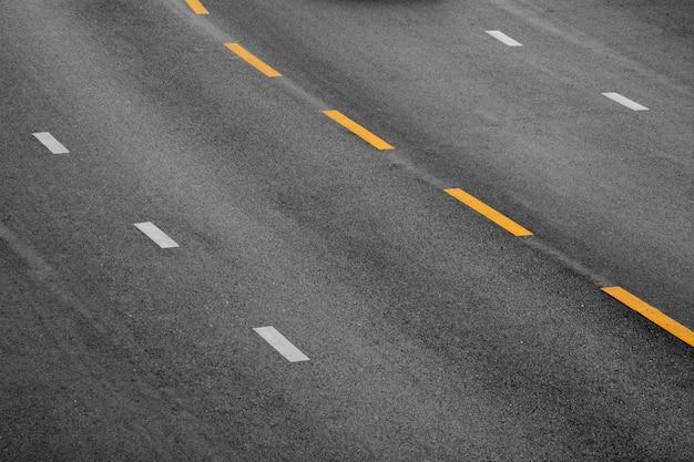 Linha de tinta amarela e branca no asfalto negro Foto Premium