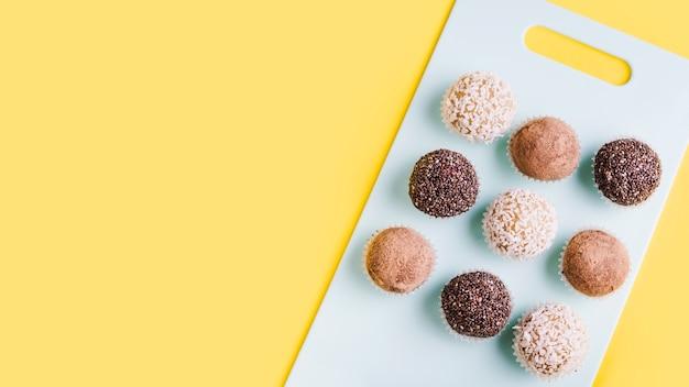 Linha de trufas de chocolate na tábua de cortar branca contra um fundo amarelo Foto Premium