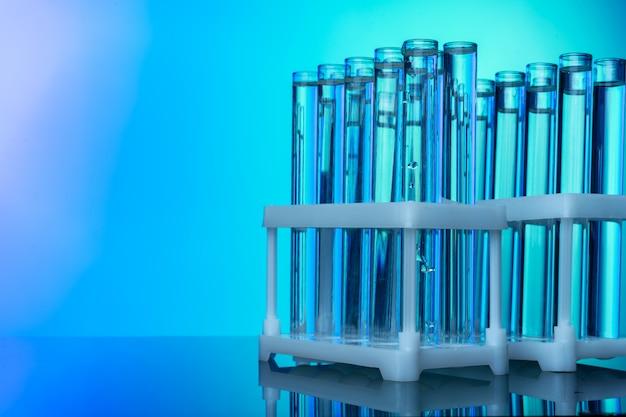 Linha de tubos de ensaio com líquidos em fundo tonificado azul e verde Foto Premium