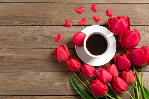 Linha de tulipas vermelhas e xícara de café preto americano em fundo de madeira dia das mães Foto Premium