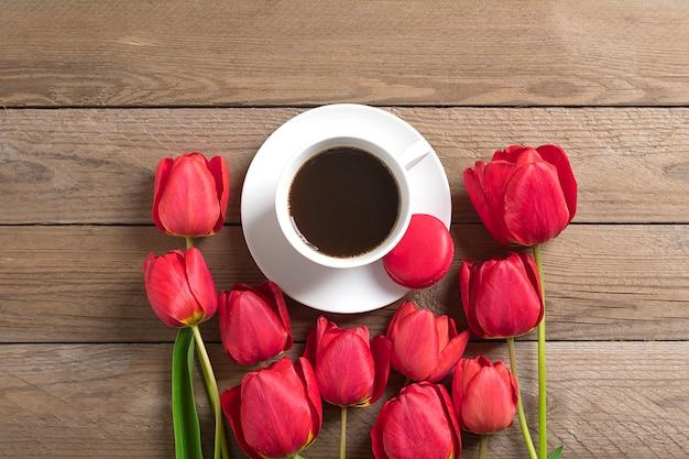 Linha de tulipas vermelhas e xícara de café preto americano em fundo de madeira flat lay Foto Premium