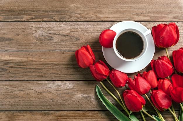 Linha de tulipas vermelhas e xícara de café preto americano em fundo de madeira Foto Premium
