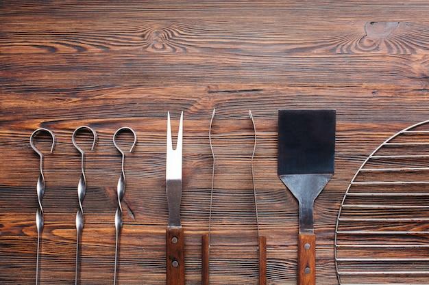 Linha de utensílios de churrasco na mesa de madeira Foto gratuita