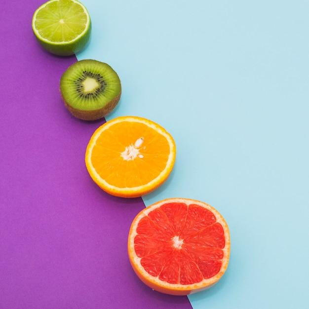 Linha inclinada de frutas cítricas e kiwi em fundo azul e roxo dual Foto gratuita
