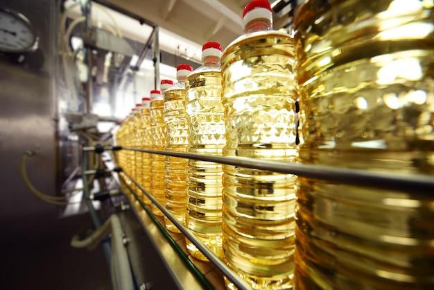 Linha ou transportador para produção de alimentos de óleo de girassol. garrafas com óleo vegetal close-up contra a superfície de equipamentos de fábrica Foto Premium