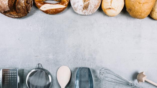 Linha superior de pães e utensílios de utensílio de cozimento em fundo branco grunge Foto gratuita