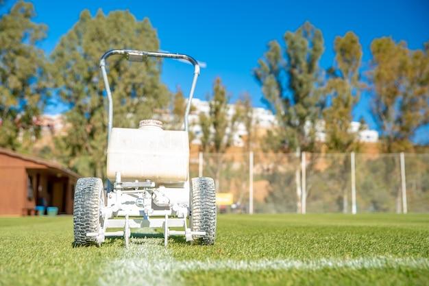 Linhas brancas desenhadas no campo de futebol com tinta branca na grama usando uma máquina especial antes de um jogo Foto Premium