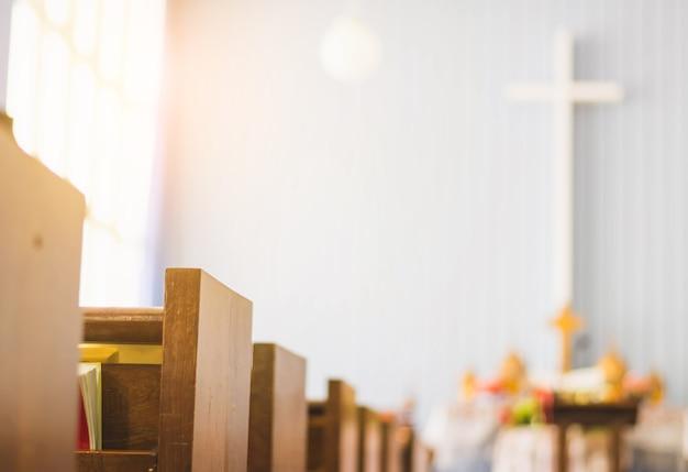 Linhas de banco de madeira vazio na igreja. foco seletivo, com fundo cruzado e gradiente Foto Premium