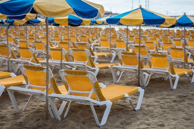 Linhas de espreguiçadeiras amarelas com guarda-sóis azuis e amarelos na praia playa de puerto rico, nas ilhas canárias Foto Premium