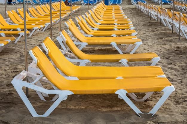 Linhas de espreguiçadeiras amarelas na praia playa de puerto rico, nas ilhas canárias Foto Premium