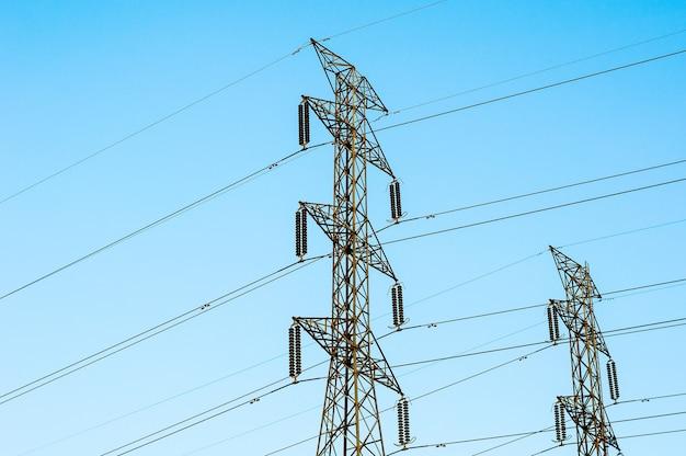 Linhas de transmissão de alta tensão isoladas no fundo do céu azul Foto Premium