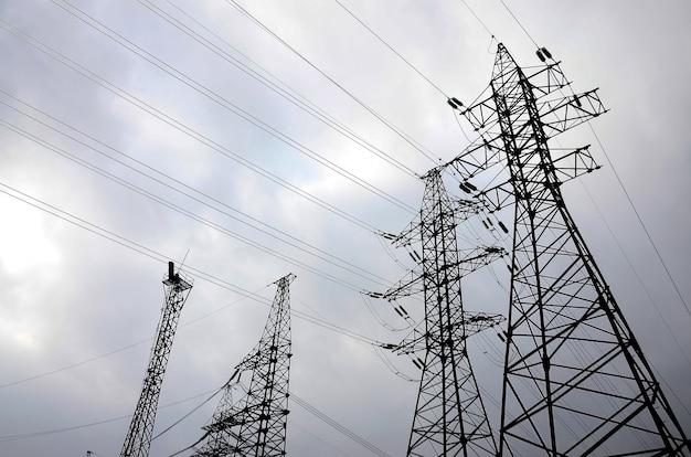 Linhas elétricas das torres de encontro a um fundo do céu nebuloso. postes de transmissão de eletricidade Foto Premium