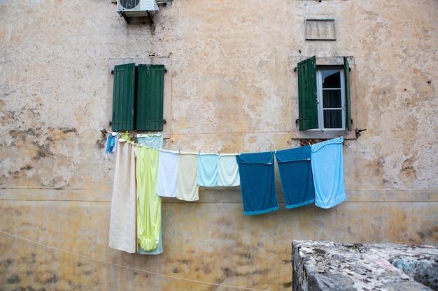 Linho multicolorido é seco do lado de fora da janela de uma casa velha Foto Premium
