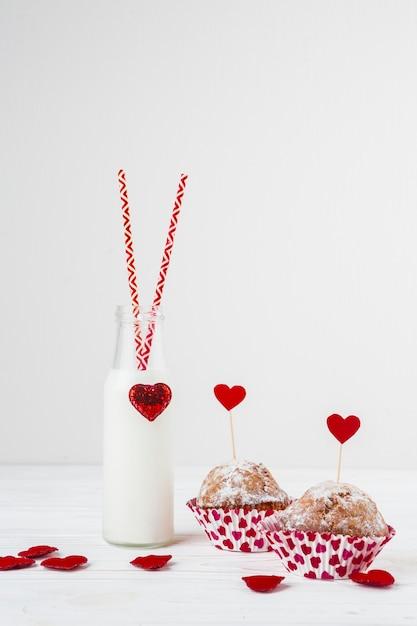 Líquido branco, em, garrafa, com, tubos, perto, bolos, com, coração, ligado, varinhas Foto gratuita