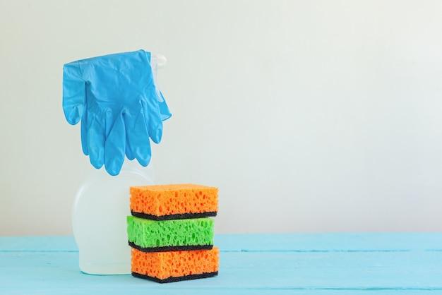 Líquido de limpeza de pulverizador branco da garrafa e esponja limpa em uma tabela. Foto Premium