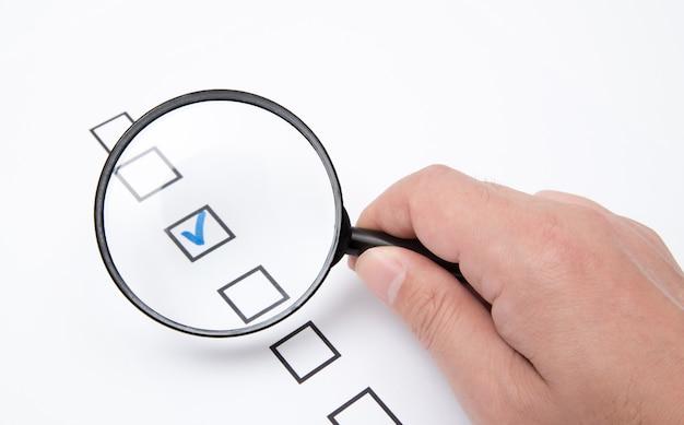 Lista de verificação em papel branco com lupa Foto Premium
