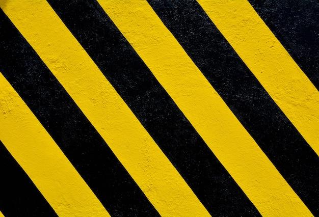 Listras amarelas e pretas na superfície de concreto - fundo Foto Premium