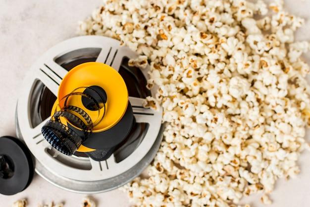 Listras de filme sobre as bobinas de filme perto das pipocas Foto gratuita