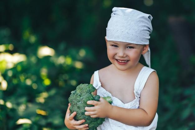 Litle feliz sorridente fazendeiro menino de macacão branco e bandana cinza segurando brócolis orgânico fresco nas mãos Foto Premium