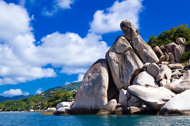 Litoral apedrejado da ilha contra o céu azul com nuvens. koh tao é Foto Premium