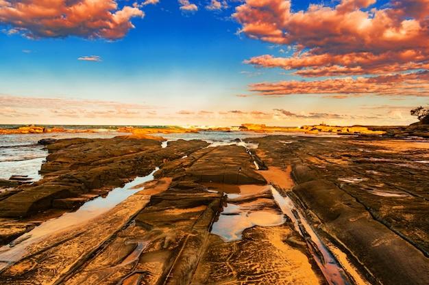 Litoral com o mar ao pôr do sol Foto gratuita
