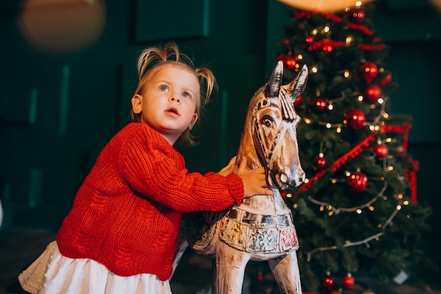 Little baby gir; l pela árvore de natal com brinquedo de madeira Foto gratuita