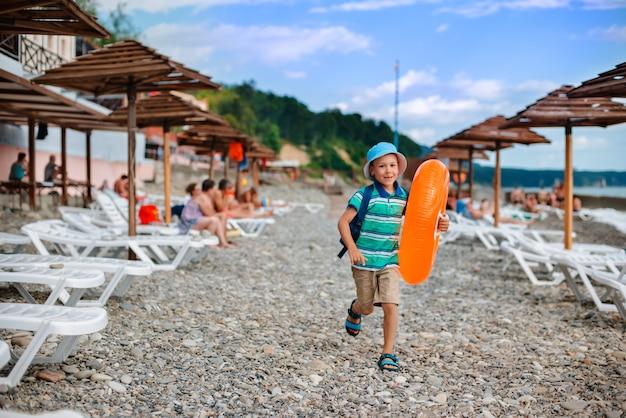 Little boy 6 anos de idade em um chapéu com um círculo laranja inflável corre Foto Premium