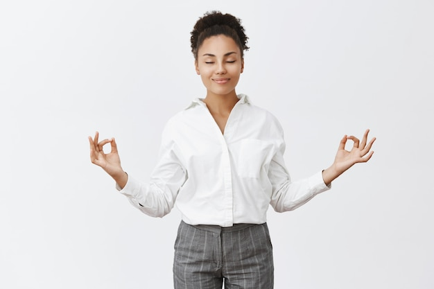 Livre de estresse, apenas paz interior. encantadora mulher relaxada e despreocupada com roupa mandona, levantando as mãos em um gesto zen, sorrindo com os olhos fechados enquanto medita ou pratica ioga, sentindo-se aliviada Foto gratuita