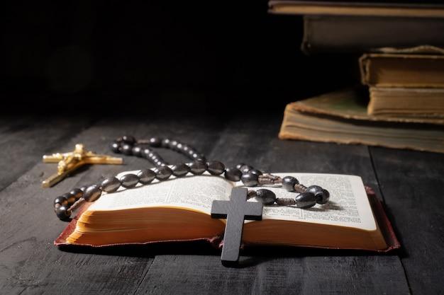 Livro aberto da bíblia e crucifixo na mesa escura. imagem discreta do novo testamento, cruz e rosário sob luz forte entre escuridão e sombras Foto Premium