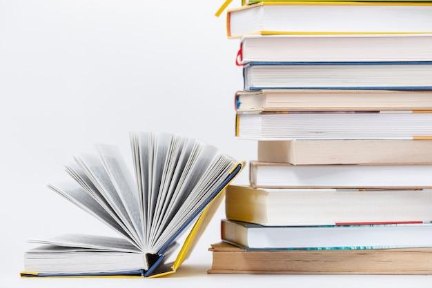 Livro aberto de cópia-espaço ao lado da pilha de livros Foto gratuita