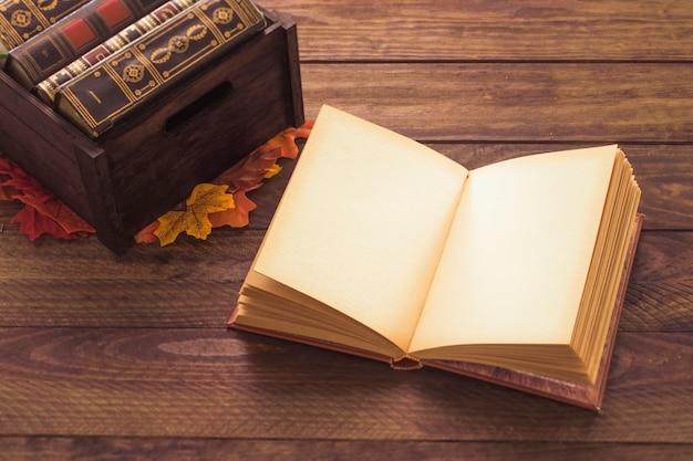 Livro aberto perto de folhas e caixa Foto gratuita