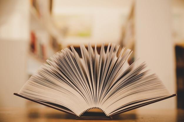 Livro aberto sobre a mesa e a ilha de estantes no fundo de sala de aula de estudo escola Foto gratuita