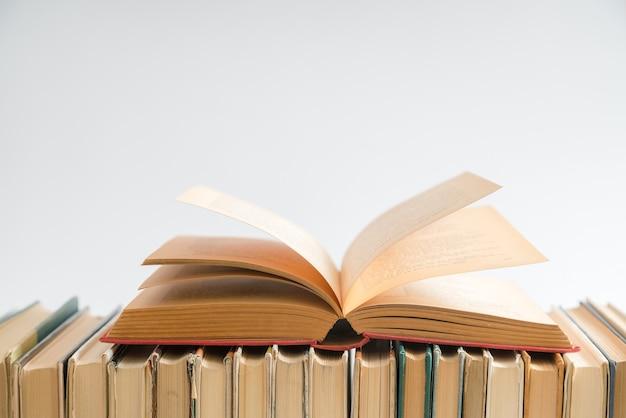 Livro aberto sobre fundo branco, livros de capa dura na mesa de madeira. Foto Premium