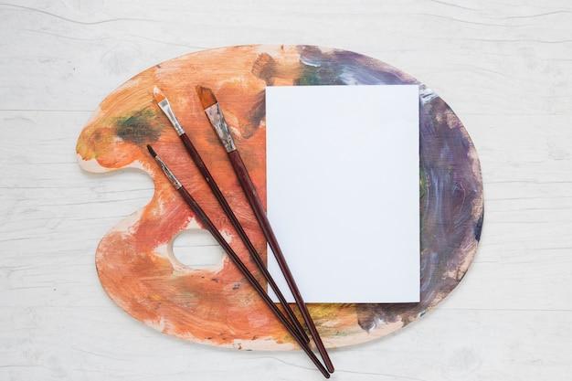 Livro branco na paleta com pincéis Foto gratuita