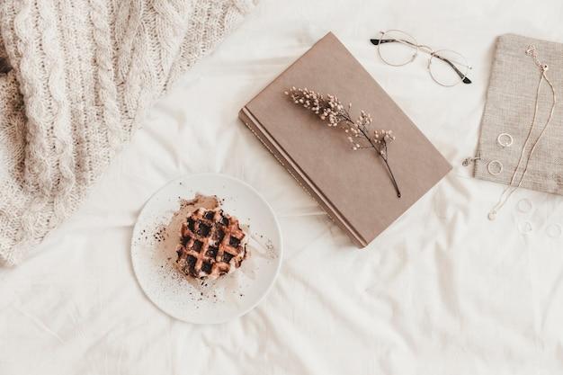 Livro com erva perto de pão na chapa e outras coisas no lençol Foto gratuita