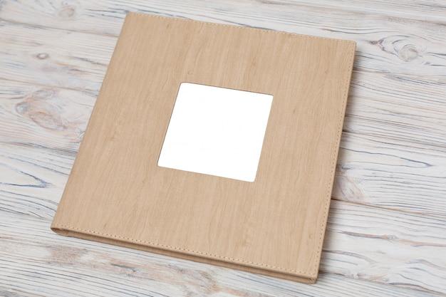 Livro de fotos com capa de couro. álbum de fotos de casamento com inserção em um fundo de madeira. Foto Premium
