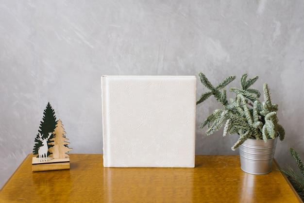 Livro de fotos de casamento em capa de couro branco, rodeado por uma árvore de natal em um balde de metal Foto Premium
