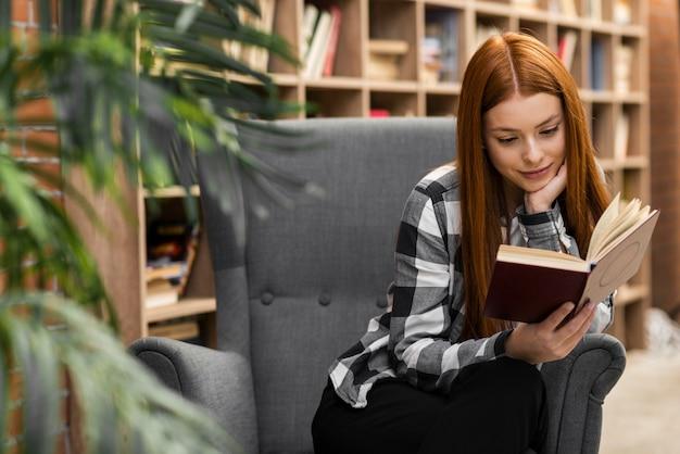 Livro de leitura adorável mulher dentro de casa Foto gratuita