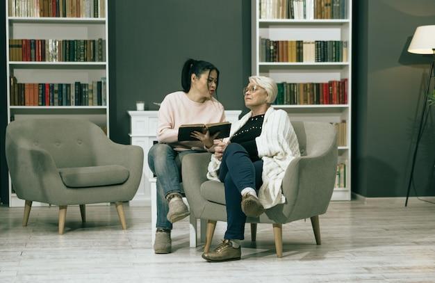 Livro de leitura da filha adulta para sua mãe idosa Foto Premium