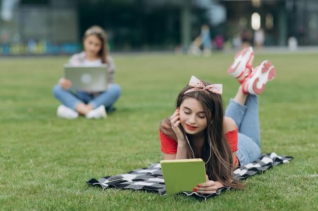 Livro de leitura da menina no parque, sentando-se na grama e descansando no campus universitário. música mulher através do fone de ouvido e livro de leitura no parque Foto Premium
