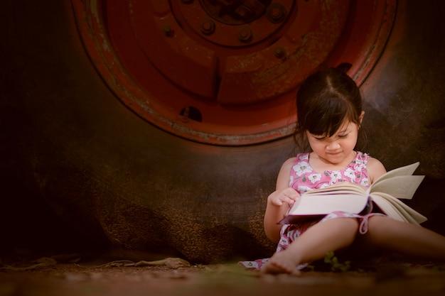 Livro de leitura da menina no tempo livre com feliz. Foto Premium