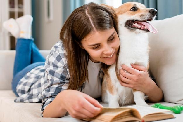 Livro de leitura da mulher no sofá com cachorro | Foto Grátis