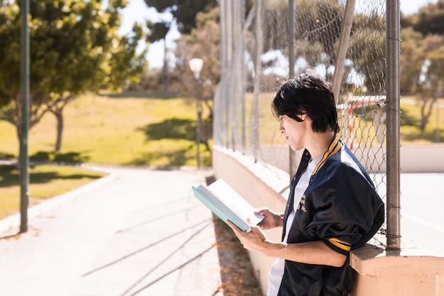 Livro de leitura de aluno étnica no beco no parque Foto gratuita