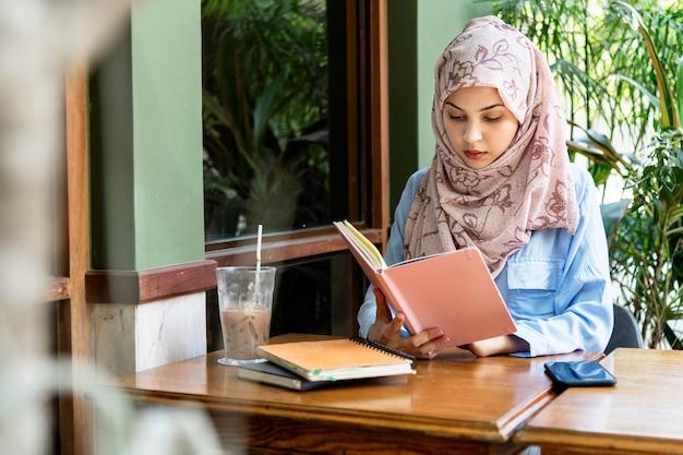 Livro de leitura de mulher islâmica Foto Premium