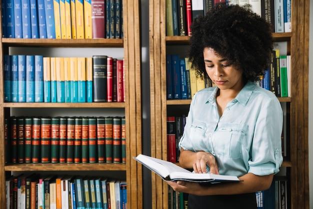 Livro de leitura de mulher negra na biblioteca Foto gratuita