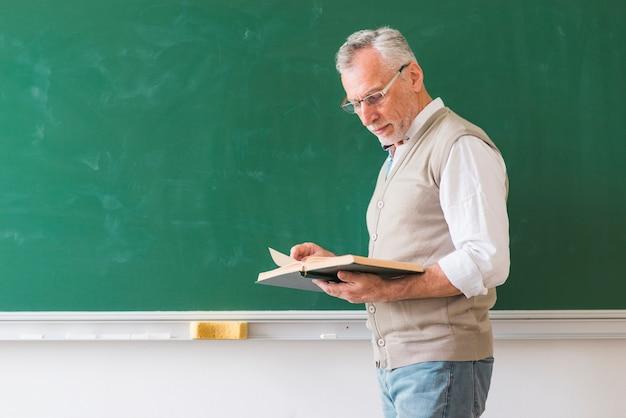 Livro de leitura de professor masculino sênior contra o quadro-negro Foto gratuita