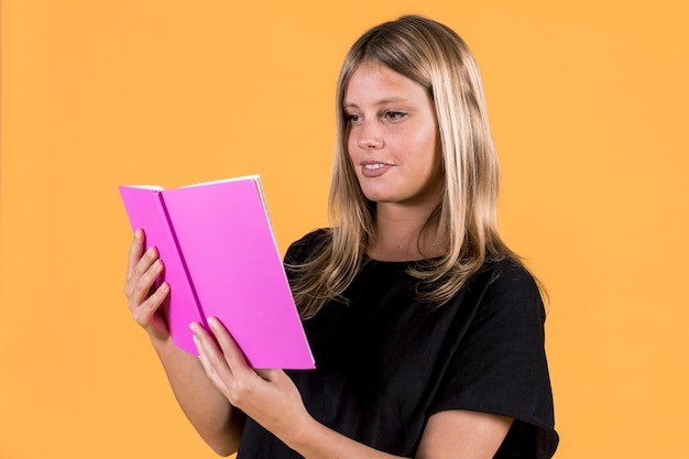 Livro de leitura feliz da jovem mulher no fundo amarelo Foto gratuita