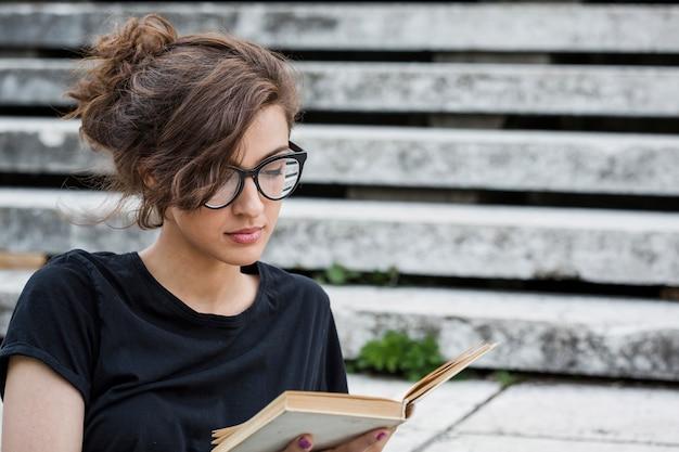 Livro de leitura feminino concentrado nas escadas Foto gratuita