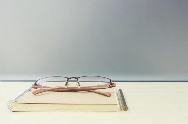 Livro de nota marrom closeup na mesa de madeira turva e parede de vidro fosco texturizada Foto Premium
