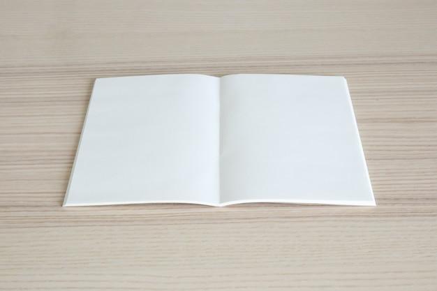 Livro de papel aberto em branco na mesa de madeira Foto Premium